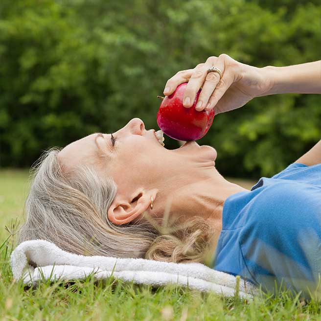 Frau beisst in Apfel | Protefix